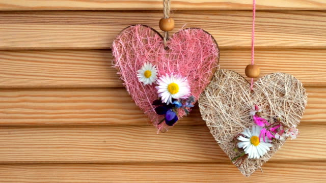 two hearts with small flowers hanging on a wooden background with copy space video
