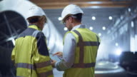 istock Two Heavy Industry Engineers Stand in Pipe Manufacturing Factory, Use Digital Tablet Computer, Have Discussion. Construction of Oil, Gas and Fuels Transport Pipeline. Back View Sparks Flying 1169738981