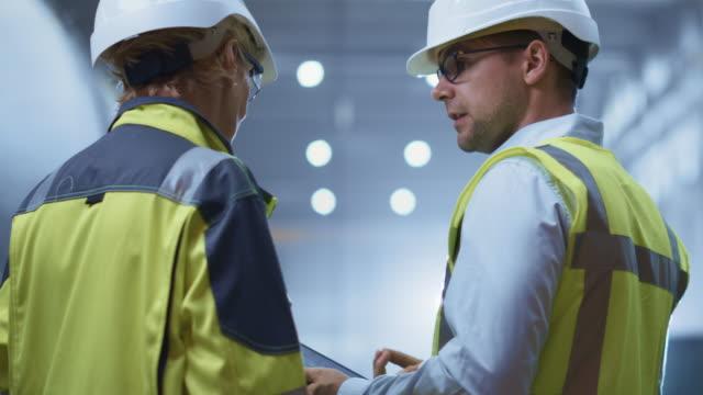 vidéos et rushes de deux ingénieurs de l'industrie lourde stand dans l'usine de fabrication de tuyaux, utiliser l'ordinateur tablette numérique, avoir des discussions. construction d'un pipeline de transport de pétrole, de gaz et de carburants. back view sparks flying (en) - fabriquer