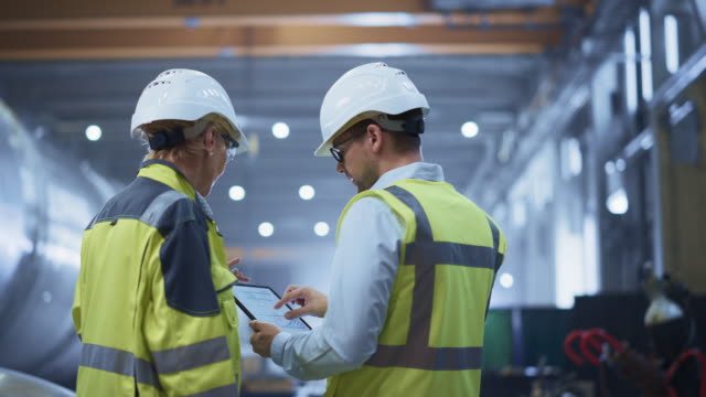 two heavy industry engineers stand in pipe manufacturing factory, use digital tablet computer, have discussion. construction of oil, gas and fuels transport pipeline. back view sparks flying - фабрика стоковые видео и кадры b-roll