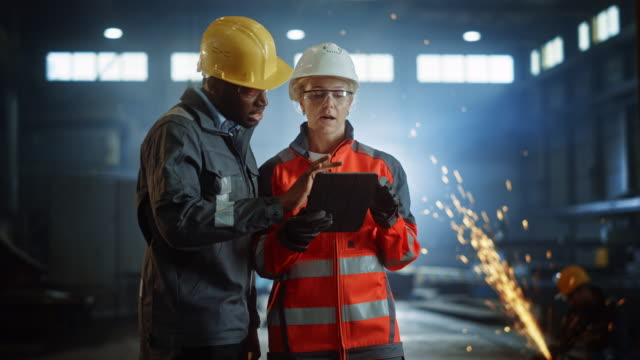Two Heavy Industry Engineers Stand in Steel Metal Manufacturing Factory, Use Digital Tablet Computer and Have a Discussion. Black African American Industrial Specialist Talk to Female Technician. Two Heavy Industry Engineers Stand in Steel Metal Manufacturing Factory, Use Digital Tablet Computer and Have a Discussion. Black African American Industrial Specialist Talk to Female Technician. construction machinery stock videos & royalty-free footage