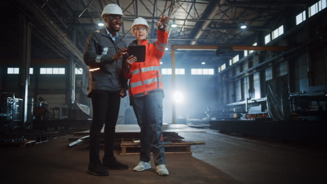 Two Heavy Industry Engineers Stand in Steel Metal Manufacturing Factory, Use Digital Tablet Computer and Have a Discussion. Black African American Industrial Specialist Talk to Female Technician. Two Heavy Industry Engineers Stand in Steel Metal Manufacturing Factory, Use Digital Tablet Computer and Have a Discussion. Black African American Industrial Specialist Talk to Female Technician. manufacturing equipment stock videos & royalty-free footage