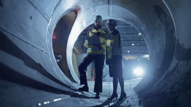 stockvideo's en b-roll-footage met twee zware industrie ingenieurs lopen inside pipe, gebruik laptop, hebben discussie, het controleren van ontwerp. aanleg van de transport leiding olie, aardgas en biobrandstoffen. industriële productiefabriek - metaalbewerking