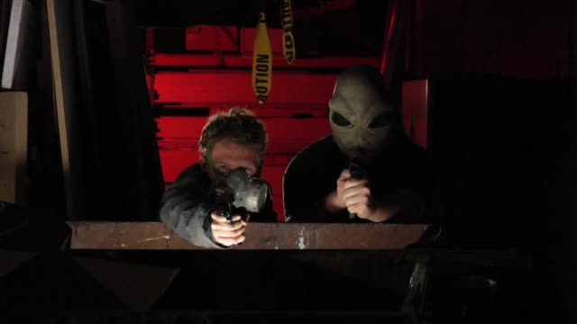 Two henchman shoot guns from behind a dumpster Two henchman crouching behind a dumpster take aim and fire their weapons.  One of the henchman is wearing a gas mask because of the tear gas in the air.  The other henchman is an alien.  In the end they both get shot and killed. The shot can be interpreted as a parody of gun fights in modern cinema.  The background is lit with Hong Kong red.  Shot in slow motion on an HVX200 in 720p in 24fps. dumpster fire stock videos & royalty-free footage