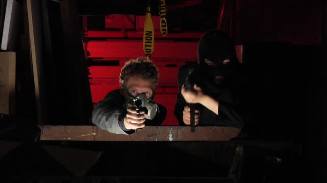 Two henchman with weapons shooting behind a dumpster Two henchman crouching behind a dumpster take aim and fire their weapons.  One of the henchman is wearing a gas mask because of the tear gas in the air.  The other henchman is has a ski mask.  He gets shot and falls back.  The background is lit with Hong Kong red.  Shot in slow motion on an HVX200 in 720p in 24fps. dumpster fire stock videos & royalty-free footage