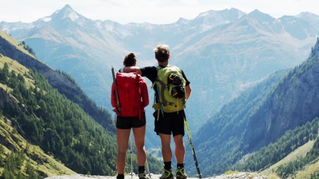 vídeos de stock, filmes e b-roll de dois caminhantes que enfrentam uma vista bonita da montanha - áustria