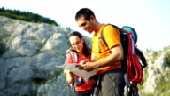 istock two hikers planning their trip with map 1258000413