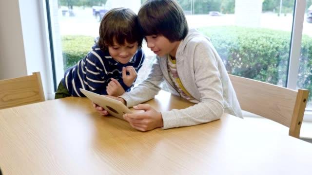 vídeos y material grabado en eventos de stock de dos hermanos hispanos miran la tableta digital mientras están en la biblioteca de la escuela - escuela media