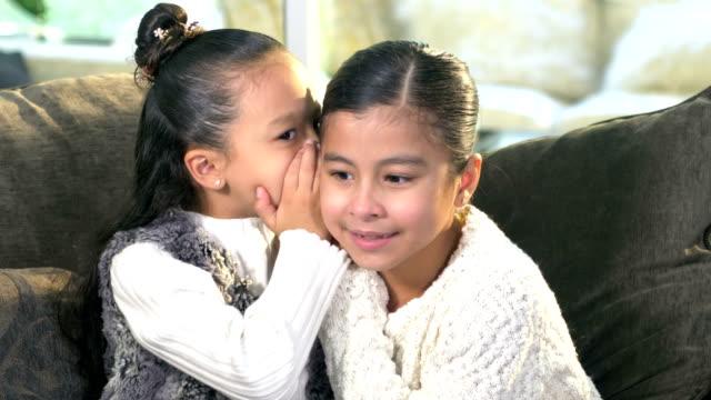 due sorelle ispaniche che si sussurrano segreti l'una all'altra - ear talking video stock e b–roll
