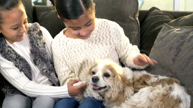Two Hispanic sisters with their dog on couch