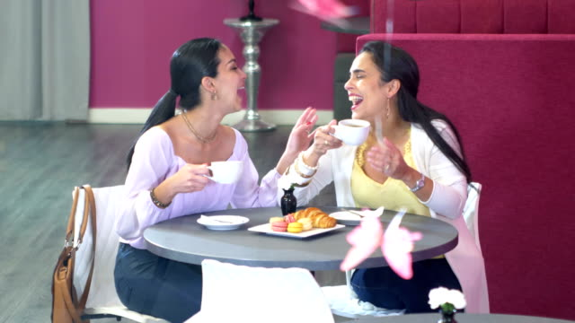 Two Hispanic woman chatting over coffee, pastries
