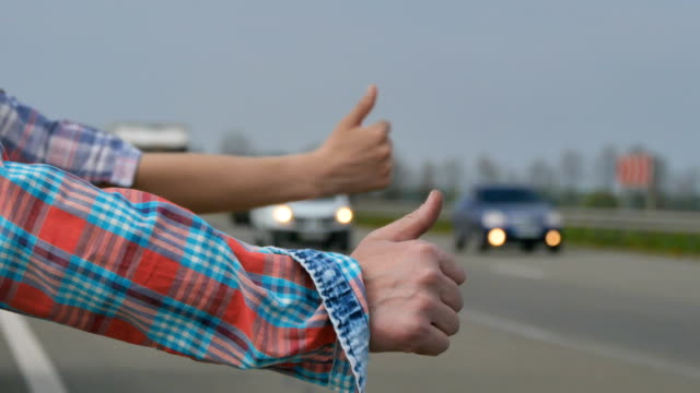 Two hitchhikers catches the car with thumbs up