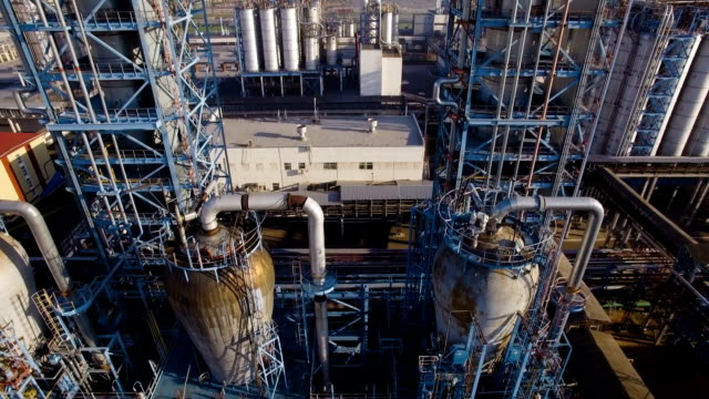 Two huge towers distillation pipes and tanks at the refinery. Aerial view video