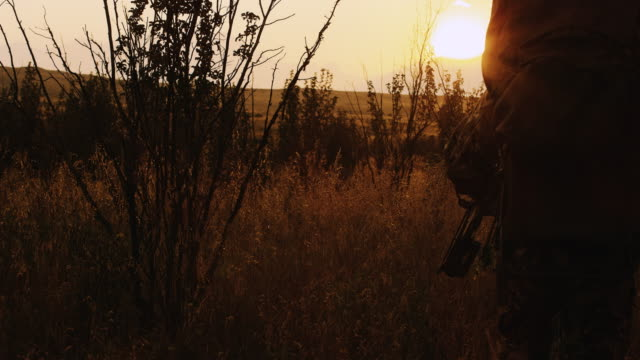 two hunters pass by the camera as they stalk their prey at sunset. - hunting stock videos and b-roll footage