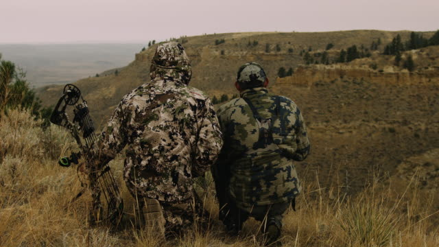 Two hunters sit, silhouetted against the rugged mountain terrain they are hunting. Their camouflage makes they almost disappear into the surroundings.
