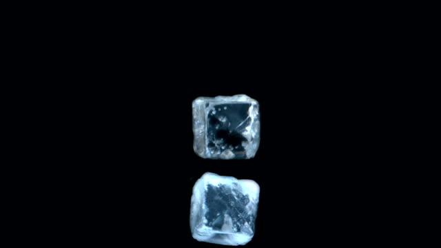 two ice cubes falling on black background - küp buz stok videoları ve detay görüntü çekimi