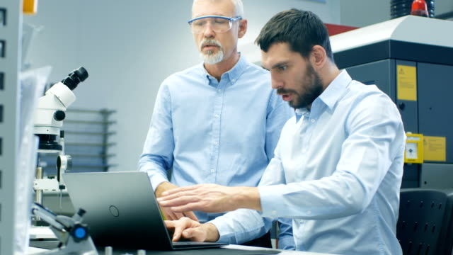 Two Industrial Scientists/ Engineers/ Technologists Have Discussion while Working on Laptop Computer. In the Background Modern Laboratory/ Factory Equipment. Two Industrial Scientists/ Engineers/ Technologists Have Discussion while Working on Laptop Computer. In the Background Modern Laboratory/ Factory Equipment. Shot on RED EPIC-W 8K Helium Cinema Camera. electrical equipment stock videos & royalty-free footage