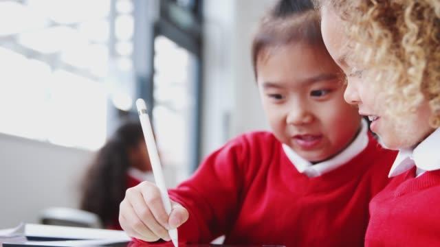 due ragazze della scuola dell'infanzia che disegnano con tablet computer e stilo in classe, primo piano, messa a fuoco rack - rack focus video stock e b–roll