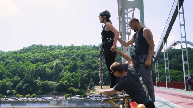 two instructors prepare the girl for a jump - bungee jumping video stock e b–roll