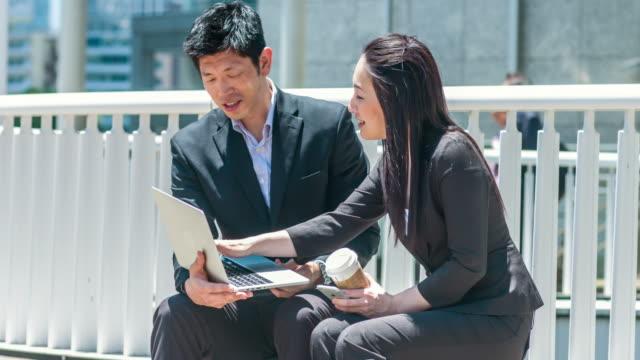 vidéos et rushes de deux personnes d'affaires japonais travaillant avec un ordinateur portable - seulement des japonais