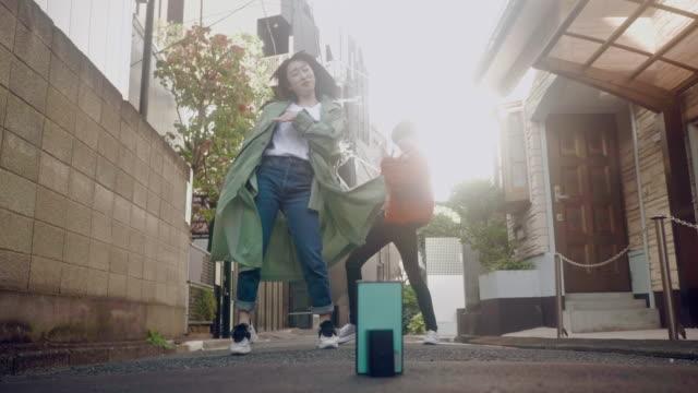 two japanese friends making dancing videos (slow motion) - cultura della gioventù video stock e b–roll