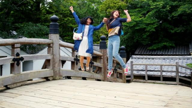 2 つの日本人女性観光客が喜びのためにジャンプ ビデオ