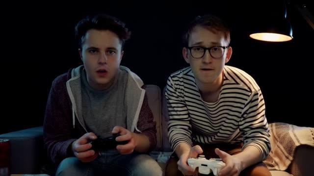 vídeos de stock e filmes b-roll de two joyful gamers win in a game of chance - man joystick