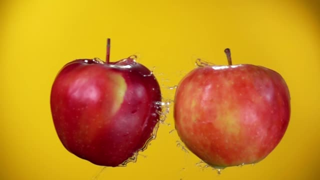 Two juicy red apples are colliding on the yellow background Two juicy red apples are flying towards each other, colliding on the yellow background and raising splashes of water in slow motion apple fruit stock videos & royalty-free footage