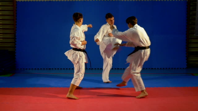 Two karate fighters attacking another and practicing self defense in slow motion video