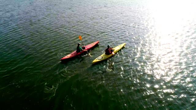 vidéos et rushes de deux kayaks naviguent le long d'une rivière pittoresque. vue aérienne. mouvement lent. - kayak