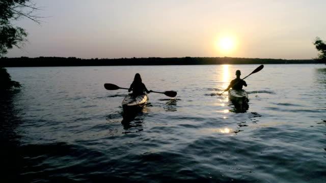vídeos y material grabado en eventos de stock de dos kayaks con la gente en el río en el pintoresco atardecer - charca