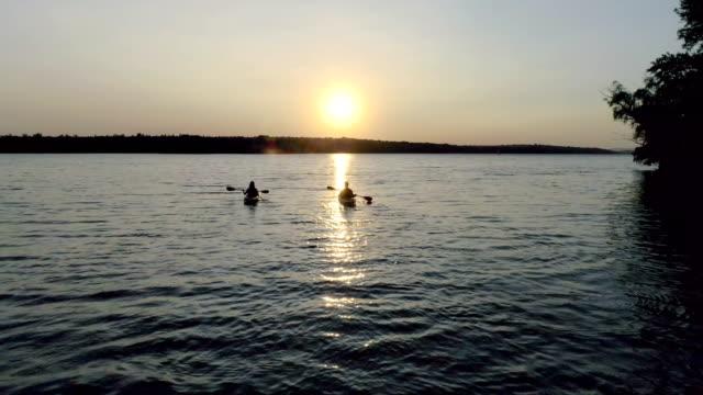 zwei kajaks mit menschen am fluss auf den malerischen sonnenuntergang - kanu stock-videos und b-roll-filmmaterial