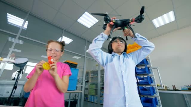 兩個孩子在實驗室裡玩四輪飛機, 無人機 - 無人飛機 個影片檔及 b 捲影像