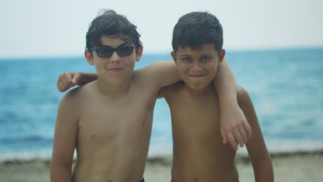 Two kids at the beach hugging and making silly faces at camera