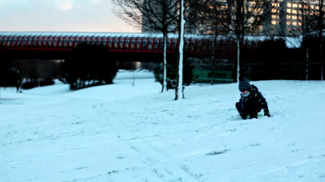 Two kids, boy brothers, sliding with bob in the snow, wintertime, happiness concept video