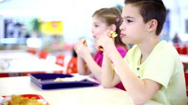 vídeos de stock e filmes b-roll de duas crianças a comer hambúrgueres. - cantina