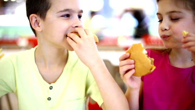 Two kids eating burgers. video