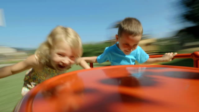 hd: two kids having fun on playground wheel - avkomma bildbanksvideor och videomaterial från bakom kulisserna