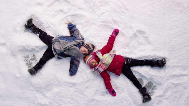 Two kids in winter making snow angels video