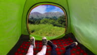 istock Two kids inside on a camping tent moving their feet and looking at the mountains during the day 1271255139