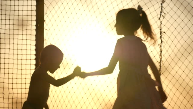 夕暮れ時のトランポリンでジャンプ 2 人の子供 ビデオ