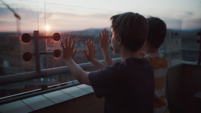Two kids on balcony looking at the sunset Two kids during COVID-19 pandemic. Kids are spending time on balcony during coronavirus outbreak. BMPCC4K RAW Q0 hope concept stock videos & royalty-free footage
