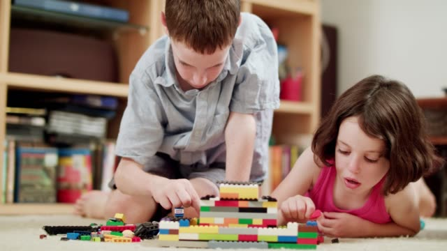 vídeos y material grabado en eventos de stock de dos niños jugando con ladrillos de lego en casa - niñas bebés