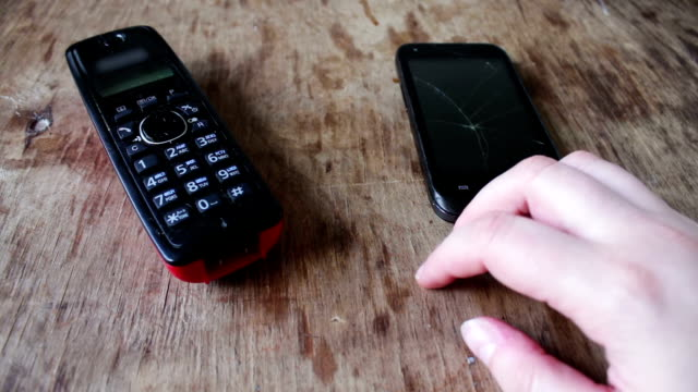 Two Kinds of phones Two different kinds of phones a modern smart phone with a broken screen and cordless phone Full HD 1920 x 1080, 29,97 fps cordless phone stock videos & royalty-free footage