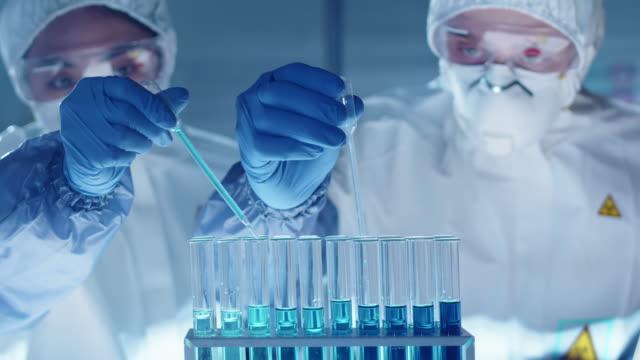vídeos de stock e filmes b-roll de two lab scientists dripping blue liquid into test tubes - biologia