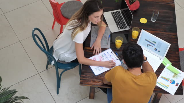 Two Latin American young entrepreneurs in office working together