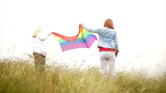 Two lesbian women in love holding rainbow flag video