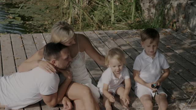 Two little boys and parents are resting on a pier near the river in a good mood. Happy family