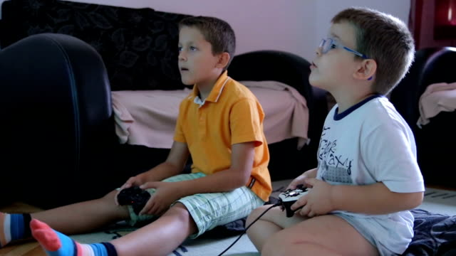 two little boys playing soccer game on gaming console and talking - brother stock videos and b-roll footage