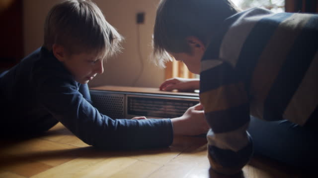 Two little boys playing with old radio.